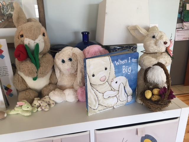 Easter bunny stuffies on the book shelf